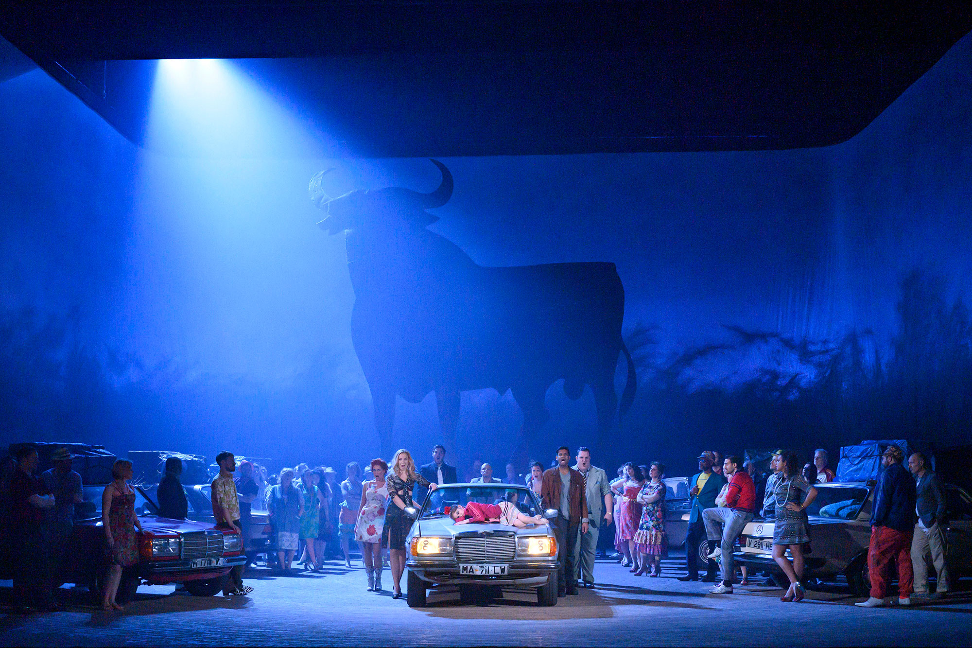 ENO Carmen 2020, ensemble shot waround cars, with silhouette of bull in background