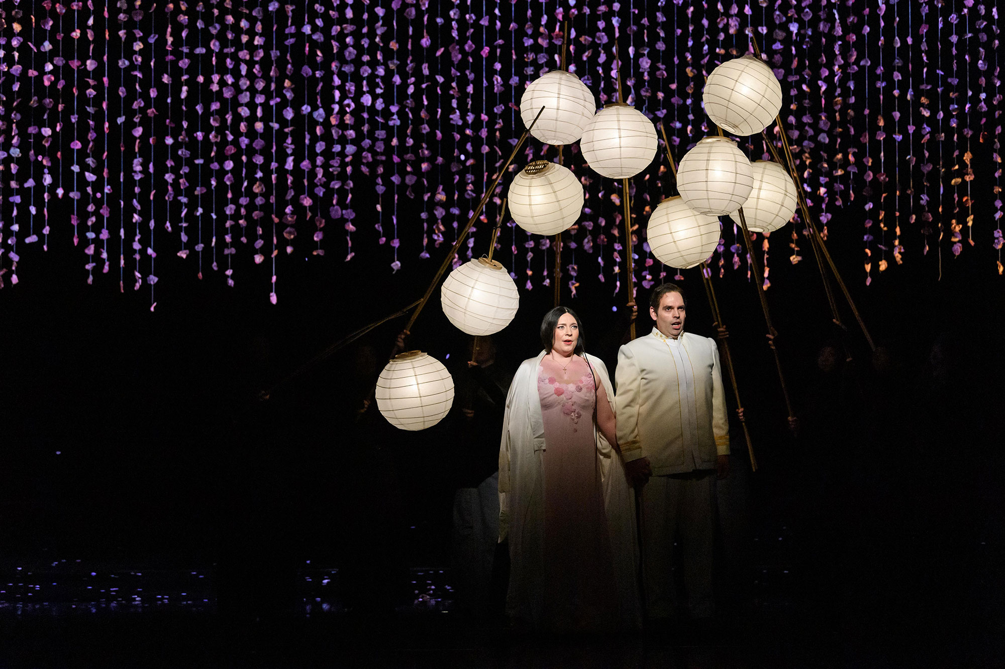 Cio-Cio San and Pinkerton stand in wedding dress, under paper lanterns casting soft light