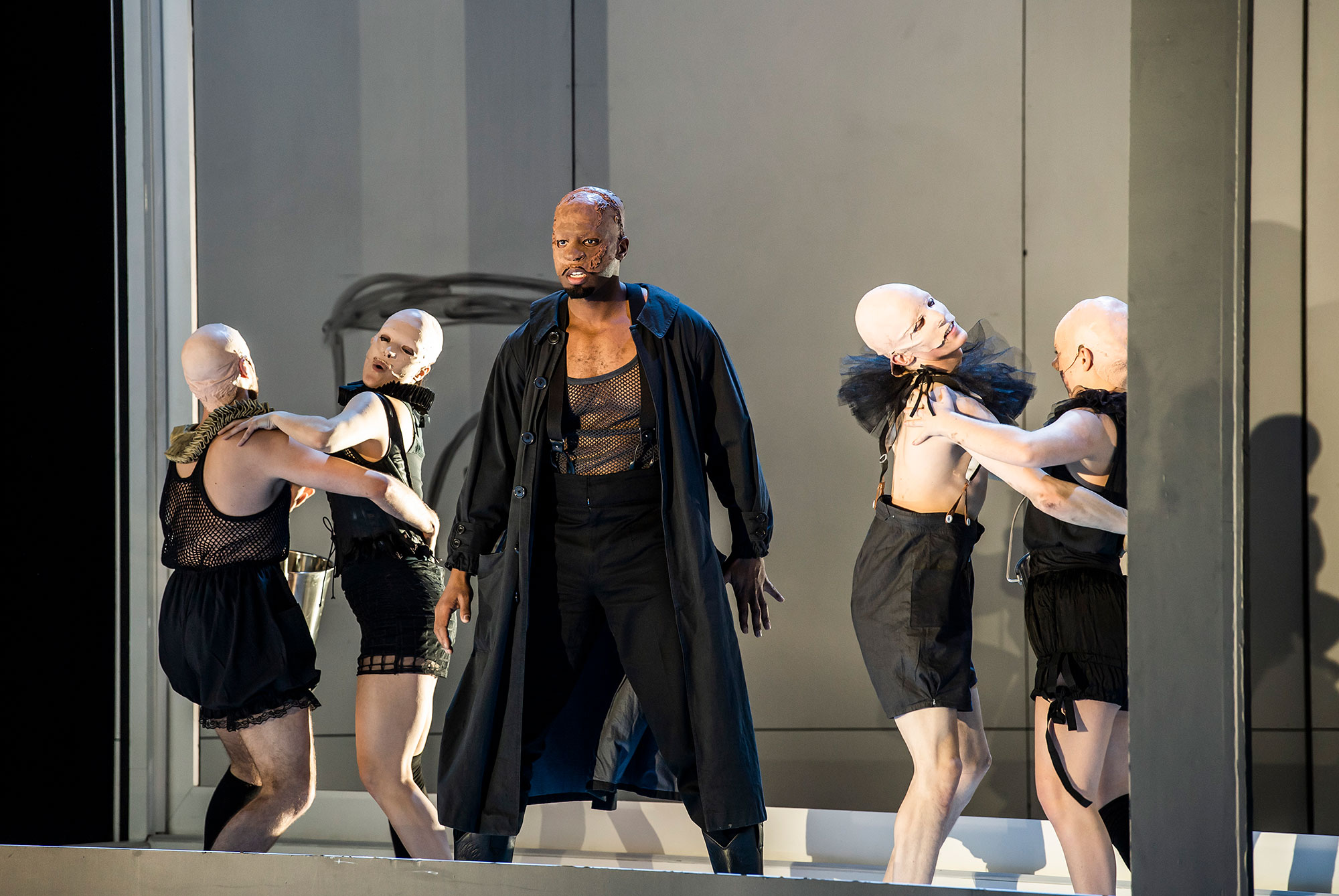 Wurm stands in front of grotesque dancers in pairs