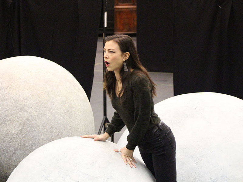 woman singing on stage in front of giant white blow up ball