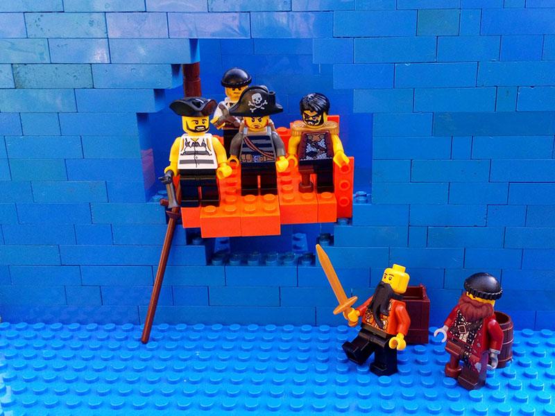 lego pirates on a lego ship coming through a lego wall