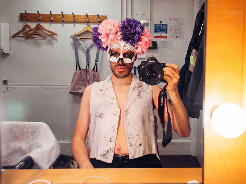 man in makeup and flower crown taking selfie in mirror with dlr camera