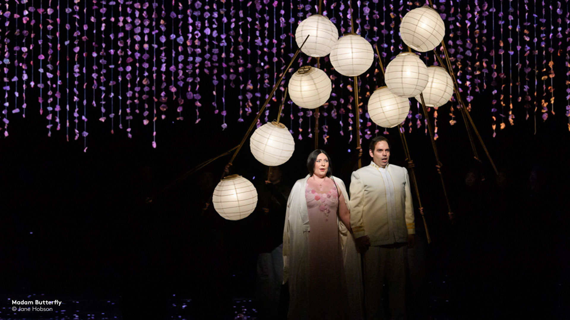 still from madam butterfly with man and woman surrounded by white lamps