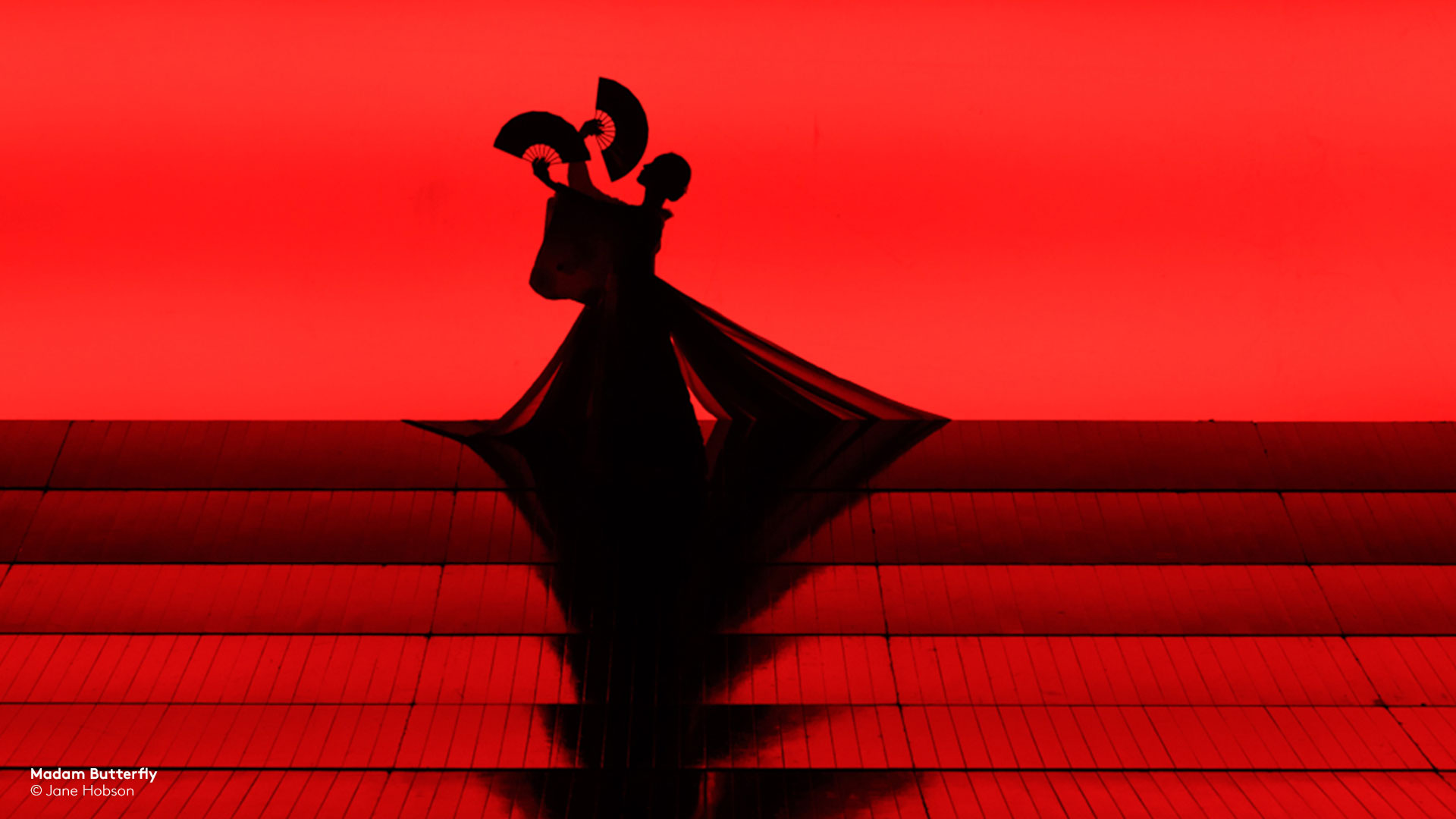 silhouette from ENO's Madam Butterfly of woman holding two fans performing on red stage