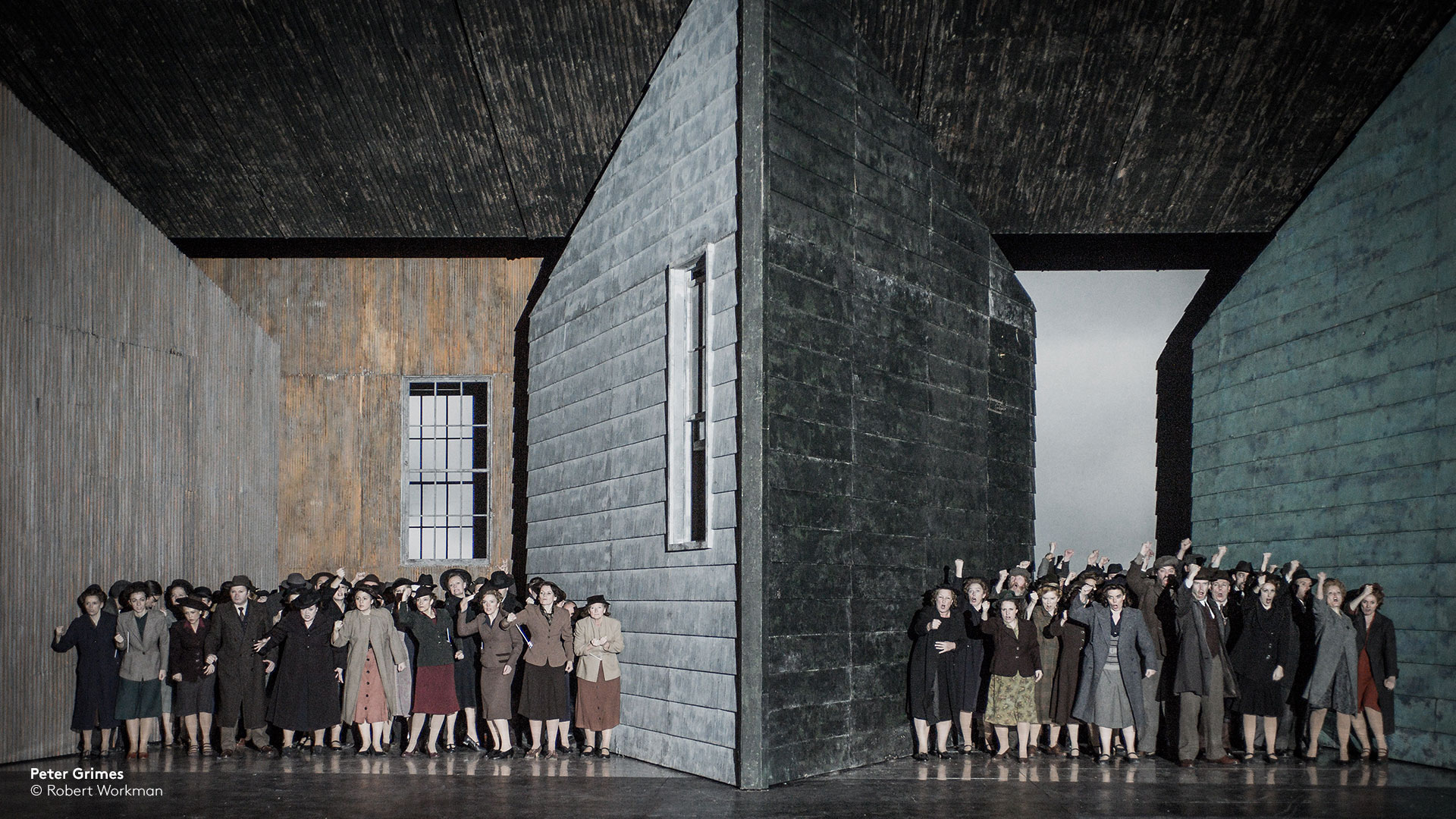 group of woman in between grey walls from ENO's Peter Grimes