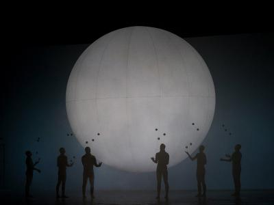 six people stood with their arms out by a giant moon