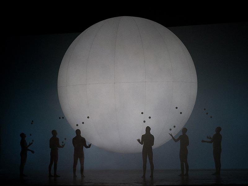 A group looking up toward a large white globe in ENO's Breathe