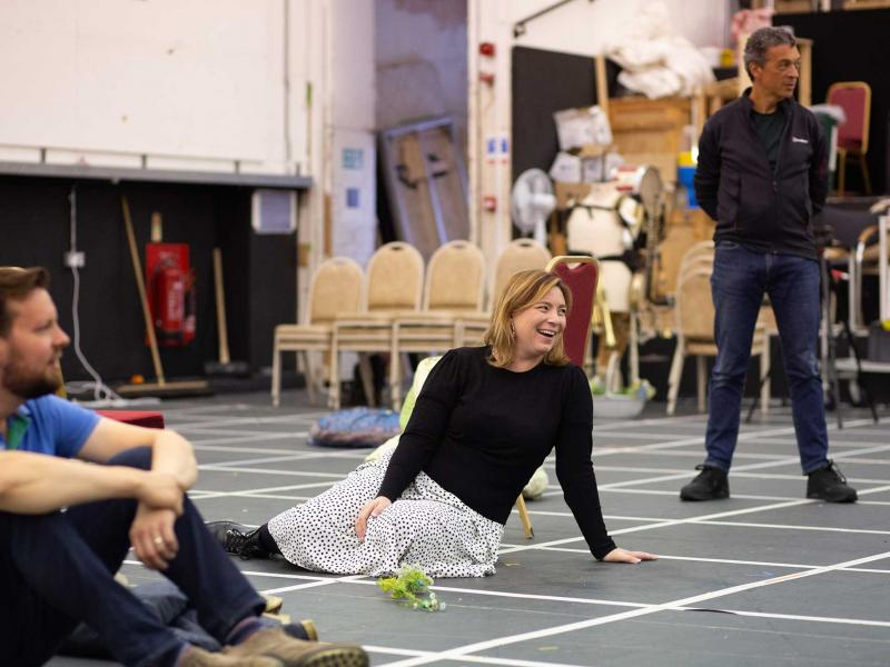 man and woman sit on the floor laughing during rehearsals of ENO Drive and Live
