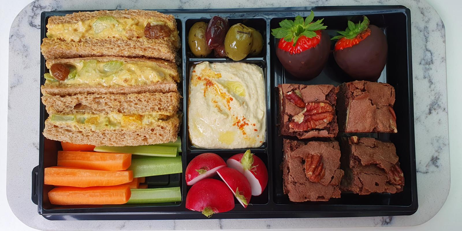 Picnic Boxes Autumn 2020 - Vegan picnic box: Celery, sultanas, apple & walnut sandwich, Hummus & crudités, Olives, Chocolate dipped strawberries, Pecan brownies