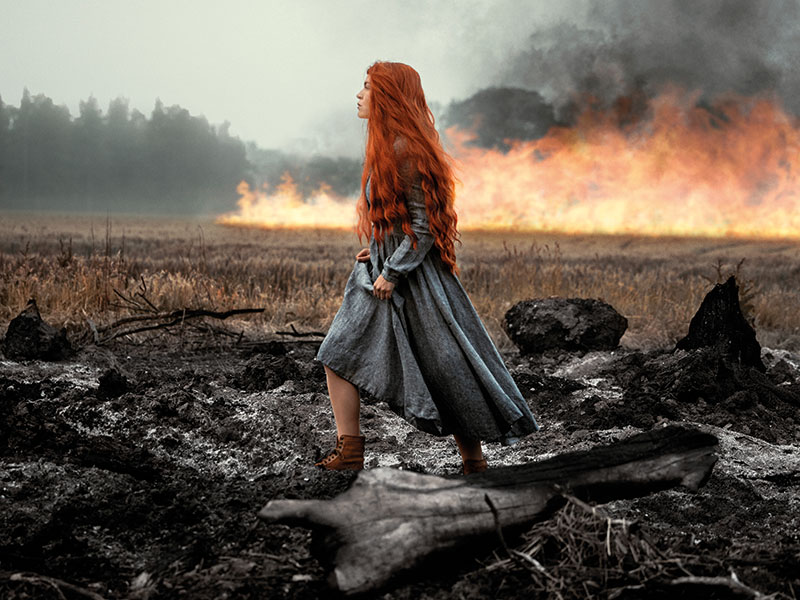 woman with long ginger hair walking through a field with fire in the background