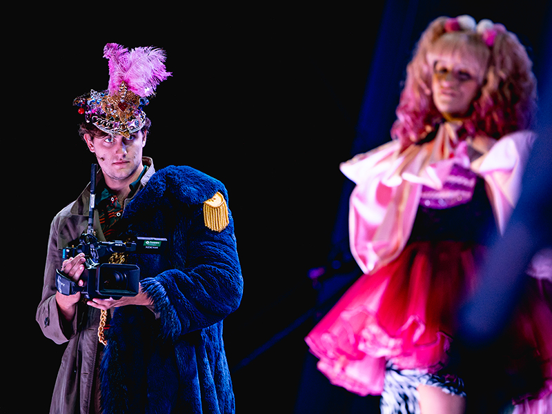 man in blue uniform on stage holding camera and filming woman in pink outfit